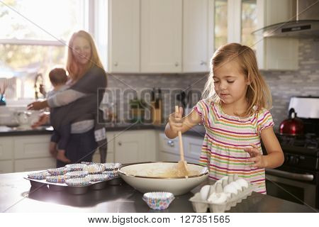 Young girl prepares cake mix, mum and baby in the background
