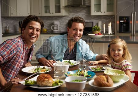 Male gay couple and daughter dining at home look to camera