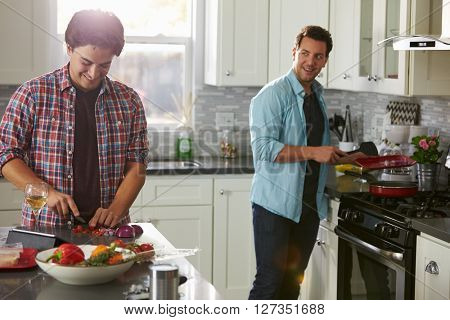 Man cooking turns to boyfriend, who is chopping ingredients