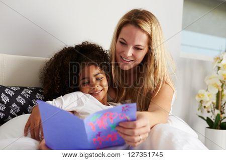 Caucasian mum and black daughter looking at birthday card