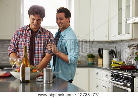 Smiling male gay couple preparing a meal at home look down