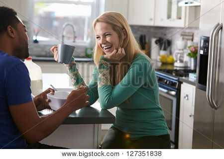 Mixed race couple talking in the kitchen, woman laughing