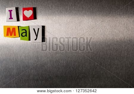 I Love May written with color magazine letter clippings on metal background. Spring concept with empty space for text.