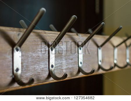 Row Of Clothes Hooks Metal On Wooden Surface