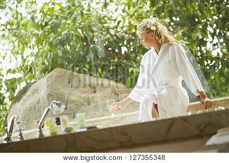 Beautiful Woman Sitting In Bathrobe In Bathroom In Luxury Hotel.