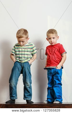 Free time fun and independence. Little boys play together indoors fit new clothes. Blonde children wear colorful clothes.