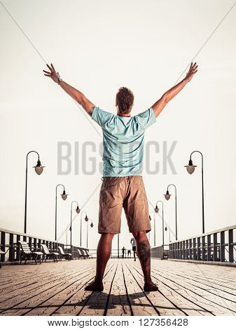 Man On Pier With Raised Hands Arms. Freedom.
