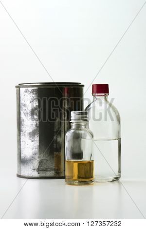 Solvents, oils, and paints used for paint, painting, and finishing. Isolated on natural white background. Focus on center bottle.