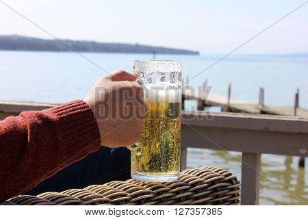 Man's hand holding the beer mug with the lake background. Drinking beer outside. Out of doors cafe beer drinking. Lake recreation zone.