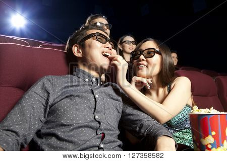 Young couple sitting at the cinema wearing 3d glasses, watching a film. Cinema photo series