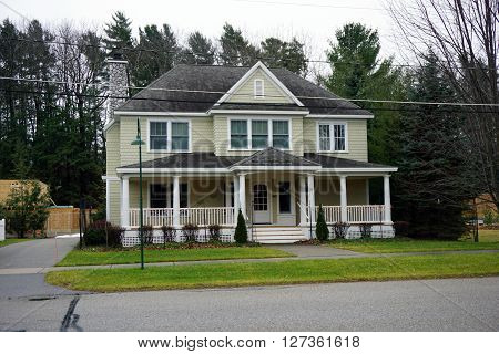 HARBOR SPRINGS, MICHIGAN / UNITED STATES - DECEMBER 23, 2015: A large white home with a front porch on Second Street in Harbor Springs.