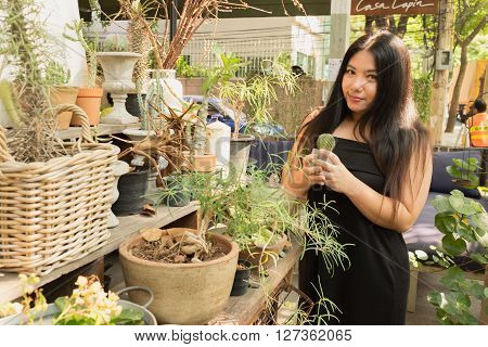 Woman in black dress standing in cactus garden fun of trees and flowers an day time with happy face/Woman in cactus garden with happy face
