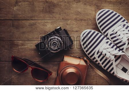 Old camera, sunglasses and sneakers on a wooden floor background. Top view