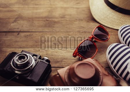 Old camera, sunglasses and sneakers on a wooden floor background.  Free space for text.