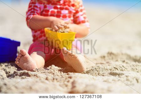 little girl play with toys on sand beach