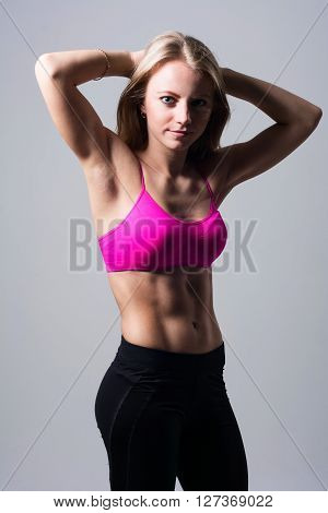 Sport girl posing in the studio. A woman shows naked body