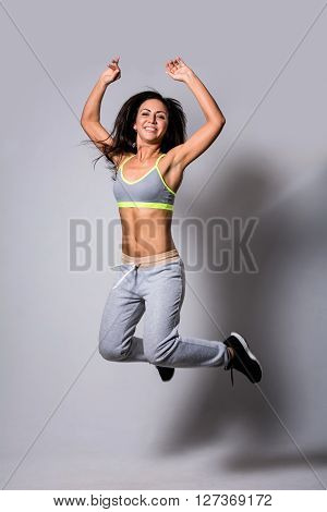 Healthy athletic woman is practicing dancing moves and jumps in the studio. Active sports lifestyle concept.