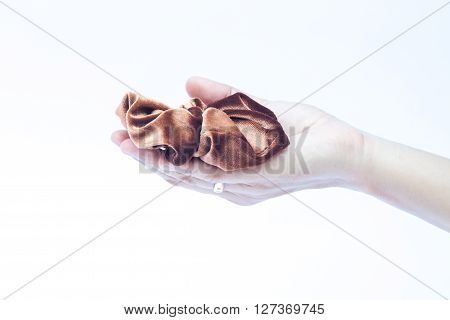 Woman hand holding hair rubber band on white background