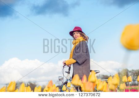 Female in a coat and hat riding bike through tulip fields in the south-west of the Netherlands. Photo taken from below