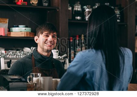 Male cashier smiling for young brunette woman in cafe