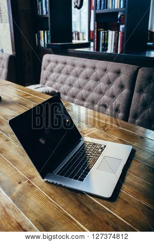 laptop standing on wooden table in cafe at morning