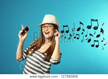 Young woman listening to music against blue background