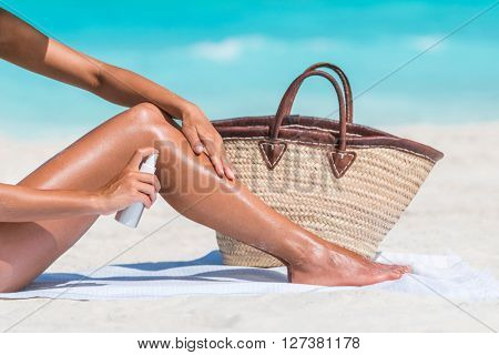 Sunscreen suntan lotion spray skincare product closeup of woman putting tanning oil on her legs. Hand holding sunblock or mosquito repellent bottle spraying on body sunbathing at beach summer vacation