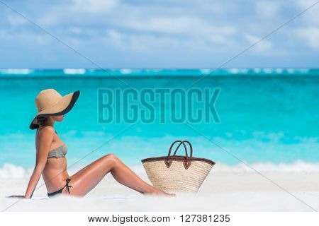 Bikini woman beach vacation sun tanning relaxing on beach. Suntan concept. Unrecognizable female adult enjoying the sunshine with straw hat sunbathing under the tropical sun on Caribbean vacation.