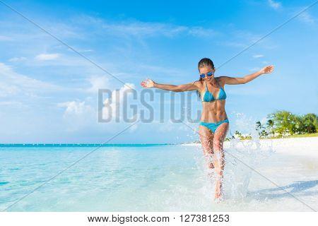 Freedom carefree girl playing splashing water having fun on tropical beach vacation getaway travel h