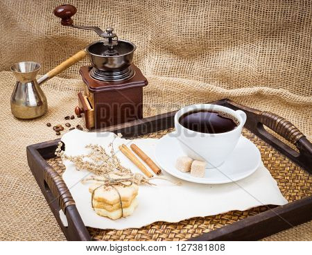 Cup of coffee coffee grinder coffee pot coffee turk cinnamon coockie on wooden tray. Sackcloth rustic background