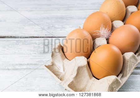 Chicken eggs in box brown eggs on wooden background with copy space
