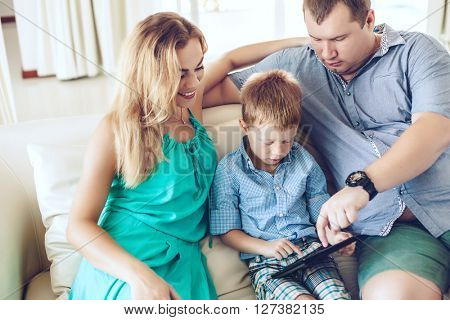 Happy family resting on a sofa and using digital tablet together in living room