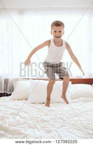 6 years old little boy is jumping on the parent's bed