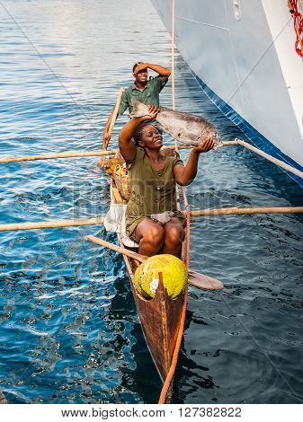 Hell-Ville Madagascar - December 19 2015: Malagasy vendors from their outrigger canoe offer crabs fish and tropical fruits to ship passengers at Hell-Ville Nosy Be Island Madagascar.