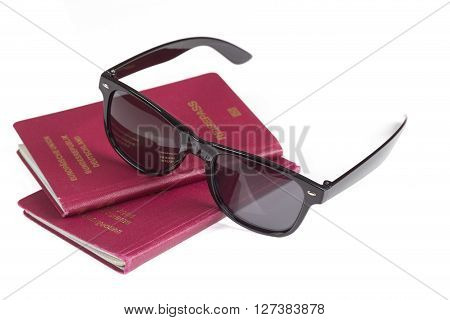 German travel passports and sunglasses over white