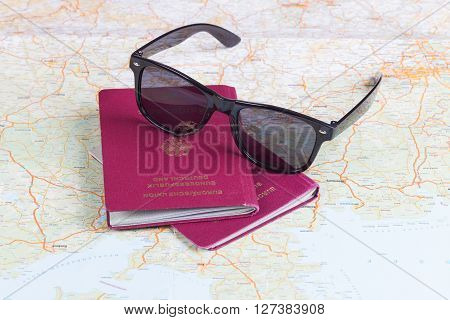 German travel passports and sunglasses over map
