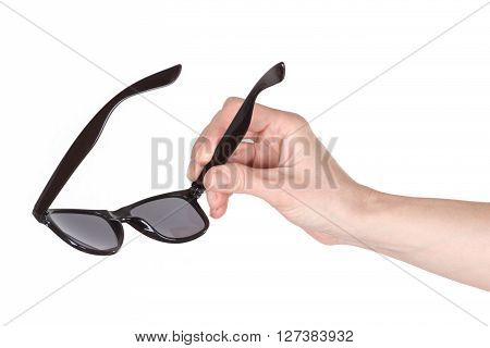 Female hand holding sunglasses over white background