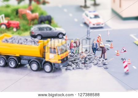 Road works with miniature workers in a countryside setting