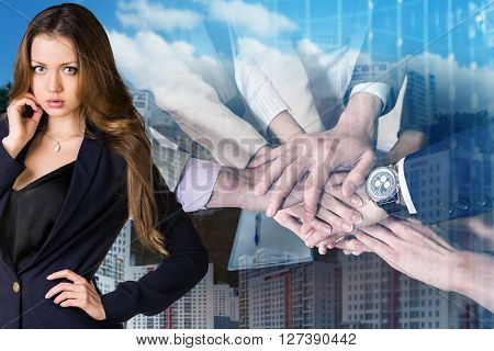 Businesswoman and business team showing unity with their hands together