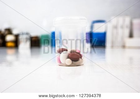 Measuring cylinder with drugs on table. Medical vials in the background.