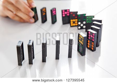Man Hands Playing Domino On Shiny Desk (focus On Domino And Blur Out Hands)