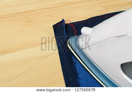 ironing blue jeanns clothing with electric iron