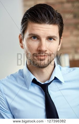 Portrait of handsome young businessman smiling, looking at camera.