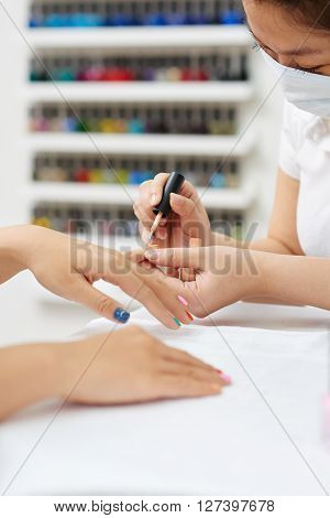 Manicurist paining nails with bright colorful nail polishes