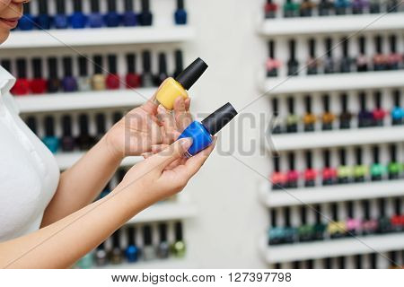 Manicurist offering pink or blue nail polish to the client