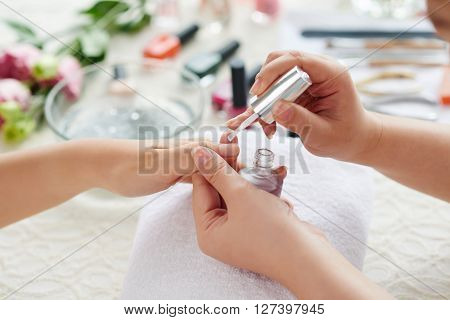 Manicurist applying transparent base coat to nail