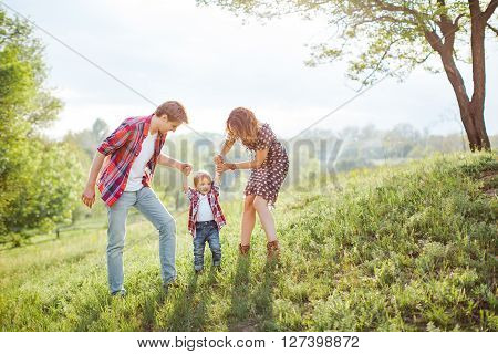 Photo of a young family enjoying holidays in the park on a sunny summer day near big family tree countryside