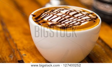 Foamy Cappuccino Coffee Cup on Wooden Table