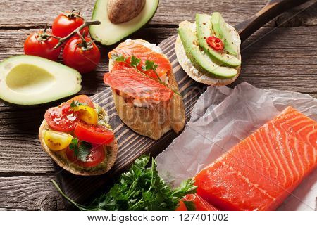 Toast sandwiches with avocado, tomatoes and salmon on wooden background