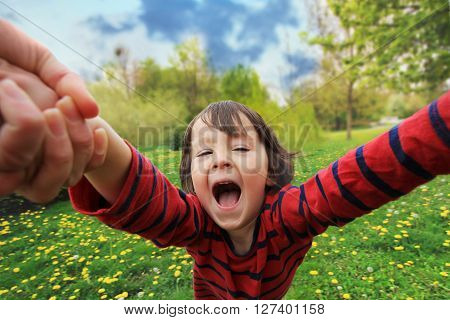 Adorable little boy, spinning in circle in the park, having fun with his mom, laughing, wide angle view